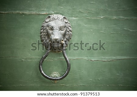 Lion shape handle and clapper on an old door - stock photo