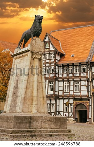 Lion statue and old timbered house in Braunschweig, Germany at sunset  - stock photo