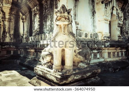 Lion statue in Ancient Ananda Temple. Amazing architecture of Buddhist Temples in Myanmar (Burma). Travel landscapes and destinations - stock photo