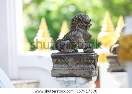 Lion statue's sitting in front of Thai temple door for protect evil. - stock photo