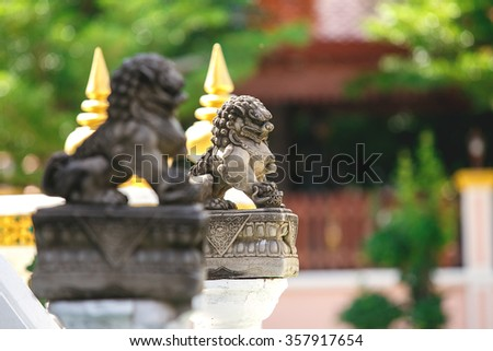 Lions statue're sitting in front of Thai temple door for protect evil.(first lion for foreground.) - stock photo
