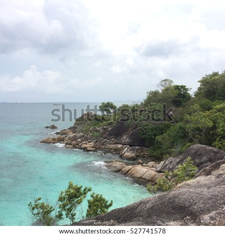 Lipe island, Thailand, with Blue and clear sea surrounded by trees in sunny day