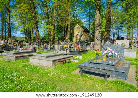 LIPNICA MUROWANA, POLAND - MAY 5, 2014: graves on a cemetery at Lipnica Murowana church. Lipnica Murowana is a famous village for pilgrims from whole Poland.