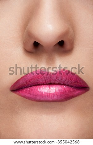 Lips with pink lipstick in close up photo. Perfect skink with gorgeous lips. Cosmetics and make up - stock photo