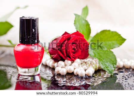 lipstick and nail polish on a background of roses, flowers, pearls and drops of water