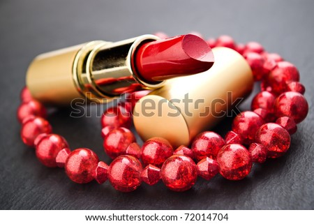 lipstick and red  jewelry on black with shallow depth of field