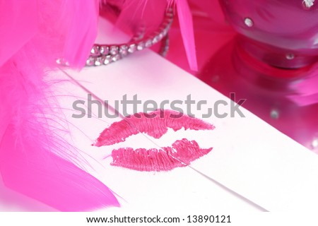 lipstick kiss on letter envelope surrounded byglamorous  pink feather boa  ( sealed with a kiss )