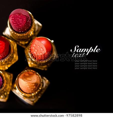 Lipsticks on black background - stock photo