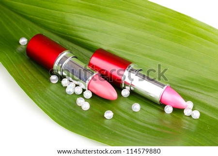 lipsticks on green leaf isolated on white