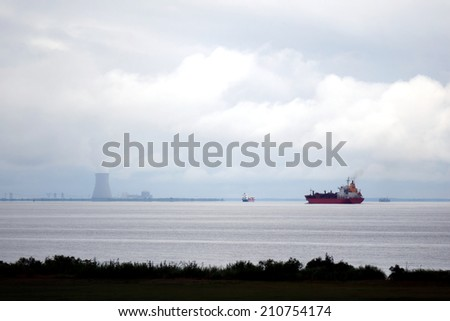 Liquefied petroleum gas tankers bulk carrier ships and cargo container vessels sailing on a river estuary near a nuclear power plant cooling tower on shore with steam cloud under stormy cloudy sky - stock photo