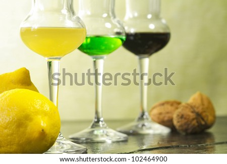 liqueur glasses with fruits over ardesia - stock photo