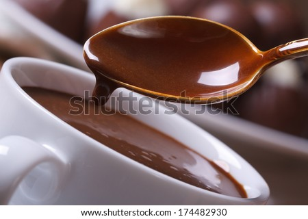 Liquid chocolate dripping from the spoon in a cup closeup horizontal. macro   - stock photo