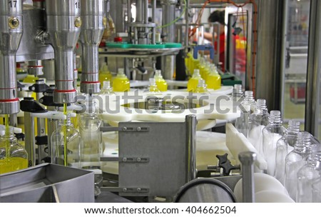 Liquid detergent on automated production line. Machinery for bottling - stock photo