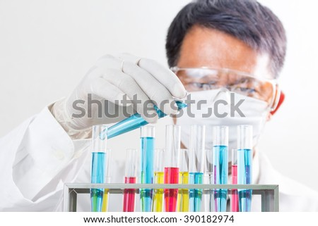 liquid dripping from pipette into test tube - stock photo