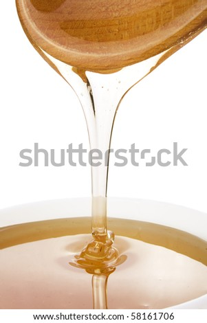 Liquid honey and wooden spoon isolated on white background
