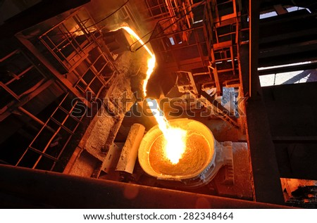 Liquid metal from blast furnace on trail - stock photo