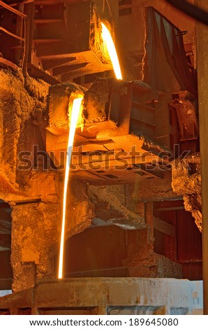 liquid metal pouring in Railroad containers inside of plant - stock photo