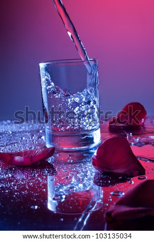 Liquid pouring into small glass. Rose petals on background - stock photo