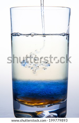 Liquid soap pouring into Glass container of Water