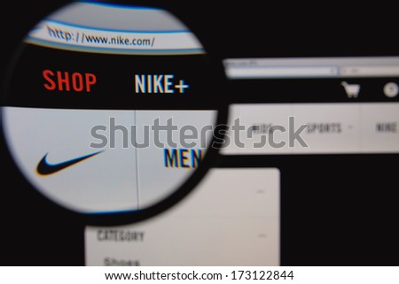 LISBON - JANUARY 26, 2014: Photo of Nike homepage on a monitor screen through a magnifying glass. - stock photo