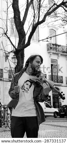 "LISBON, PORTUGAL - APRIL 22, 2015: Unidentified violinist wearing t-shirt with portrait of Amalia Rodrigues  ( known as ""Queen of Fado"") plays music at city square for the tourists and citizens."