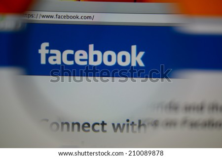 LISBON, PORTUGAL - AUGUST 3, 2014: Photo of Facebook homepage on a monitor screen through a magnifying glass. - stock photo