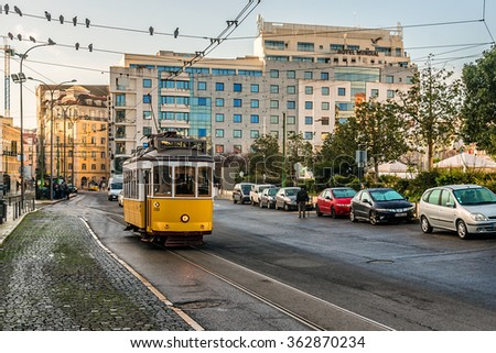 LISBON, PORTUGAL - DECEMBER 26, 2015: Famous tram 28 (Electrico 28) - vintage yellow tram goes through all over the city center, crossing many tourist attractions.