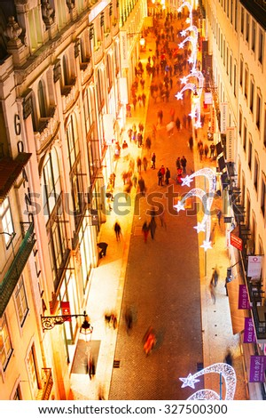 LISBON, PORTUGAL - DECEMBER 22, 2014: People on the shopping street in downtown of Lisbon in the evening. Portugal are visiting more than 7 million tourists each year. - stock photo