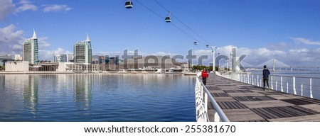 Lisbon, Portugal - February 01, 2015: People practicing sports on Passeio Ribeirinho. Atlantico Pavilion (MEO Arena). Vasco da Gama Tower and Bridge, Myriad Hotel and aerial tramway. Park of Nations - stock photo