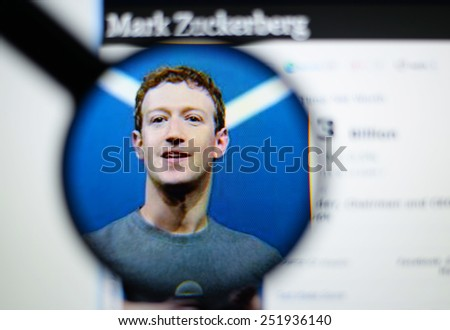 LISBON, PORTUGAL - February 12, 2015: Photo of Forbes article page about Mark Zuckerberg on a monitor screen through a magnifying glass. - stock photo