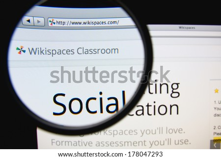 LISBON, PORTUGAL - FEBRUARY 22, 2014: Photo of Wikispaces homepage on a monitor screen through a magnifying glass.
