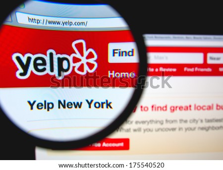 LISBON, PORTUGAL - FEBRUARY 8, 2014: Photo of Yelp homepage on a monitor screen through a magnifying glass. - stock photo