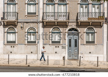 LISBON, PORTUGAL - JULY 2: man walking in front of tiled facades along the Almirante Reis Avenue close to Largo do Intendente in Lisbon, Portugal on July 2, 2017.