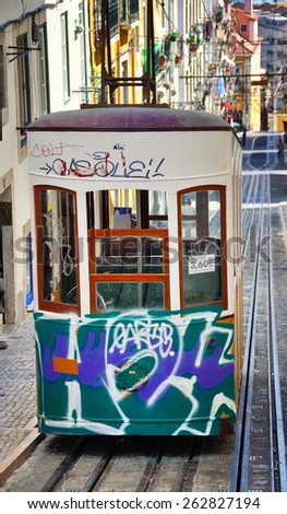 LISBON, PORTUGAL - JULY 24, 2013: The Bica Funicular painted in graffiti - the symbol of the city, operating since 1892. Designated as National Monument