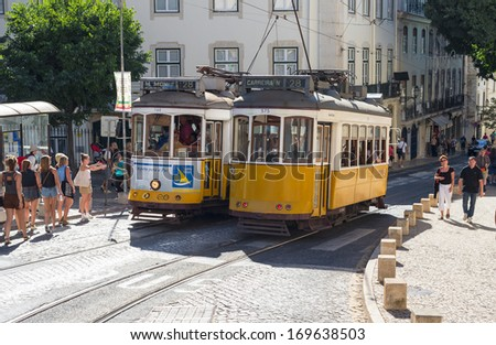 LISBON, PORTUGAL - JULY 28: Traditional yellow trams downtown Lisbon on July 28, 2013. Trams are used by everyone and also keep the traditional style of the historic center of Lisbon.