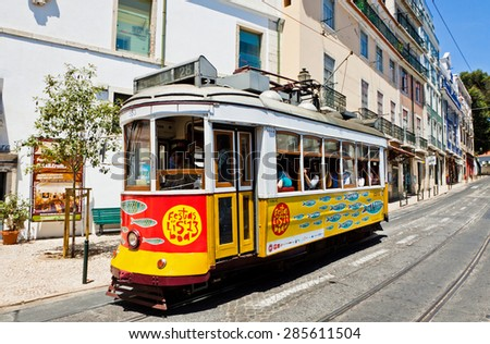 LISBON, PORTUGAL - JUNE 22, 2013: Traditional vintage Lisbon yellow tram decorated with sardines during Popular Saints Festival (Festas dos Santos Populare) in Lisbon, Portugal - stock photo