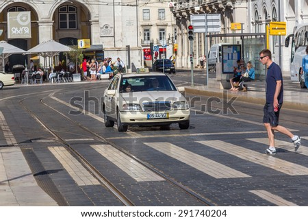 LISBON, PORTUGAL - MAY 24, 2015: An unidentified pedestrian cross a road in Lisbon, Portugal. In year 2012, 9.7 road fatalities per 100,000 inhabitants were reported in Portugal. - stock photo