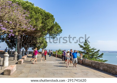 LISBON, PORTUGAL - MAY 24, 2015: Tourists walking inside Sao Jorge Castle in LIsbon, Portugal. It is a Moorish castle occupying a commanding hilltop overlooking Lisbon and Tagus River. - stock photo