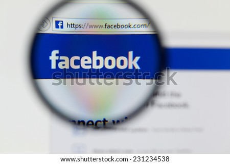 LISBON, PORTUGAL - NOVEMBER 17, 2014: Photo of Facebook homepage on a monitor screen through a magnifying glass.