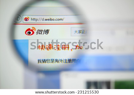 LISBON, PORTUGAL - NOVEMBER 17, 2014: Photo of Sina Weibo homepage on a monitor screen through a magnifying glass.
