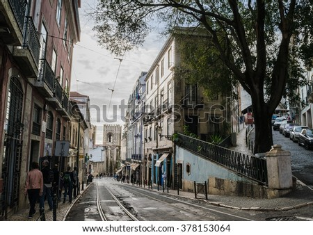 Lisbon, Portugal � Oct 2015: Romantic Lisbon street and Lisbon Cathedral on the background