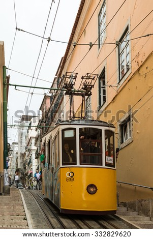 LISBON, PORTUGAL - OCTOBER 19, 2015:  A historic classic yellow tram of Lisbon built partially of wood and being secured by cable while navigating through the steep and narrow streets of old Lisbon - stock photo