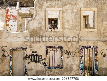 LISBON, PORTUGAL - OCTOBER 10, 2011: A ruined building near the Castelo in Lisbon is covered with graffiti. The windows frame additional drawings including a derivative image of Migrant Mother. - stock photo