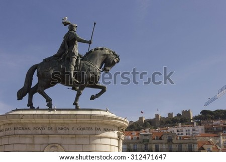 LISBON, PORTUGAL - OCTOBER 26 2014: Equestrian statue of King John I in the Praca da Figueira, Lisbon, with St. Jorge Castle in the background