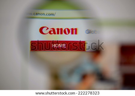 LISBON, PORTUGAL - OCTOBER 8, 2014: Photo of Canon homepage on a monitor screen through a magnifying glass.