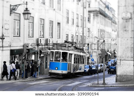 LISBON, PORTUGAL - OCTOBER 27, 2013 : Traditional vintage tram makes its way across central Lisbon streets stopping at the tram station. Black and white picture with blue elements.  - stock photo