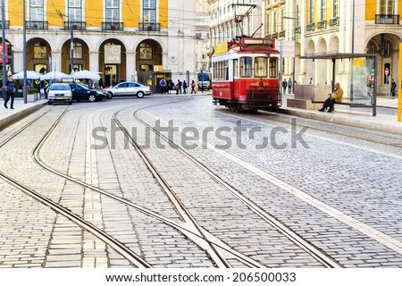 LISBON, PORTUGAL - OCTOBER 25 : Vintage tramway in the city center if Lisbon - Commerce Square with tram rails on the foreground on October 25th 2013 in Lisbon, Portugal