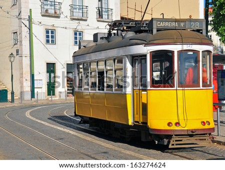 Lisbon yellow tram crosses Alfama streets