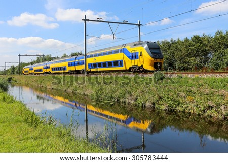 LISSE, NETHERLANDS - AUGUST 9, 2015: Dutch yellow and blue train reflected in a canal - stock photo