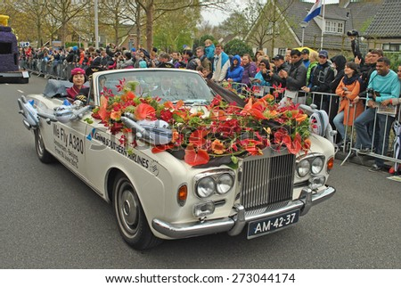 "LISSE, THE NETHERLANDS, 25 APRIL 2015 - Car with captains and stewards from China Southern Airlines in the annual Dutch flower parade ""Bloemencorso"" near the Keukenhof Gardens in The Netherlands. - stock photo"